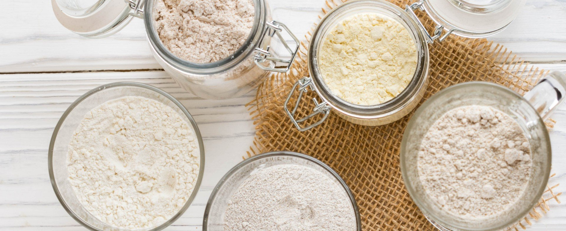 Different flour in glass jars, wheat, corn, rye, oats, spelt, flax